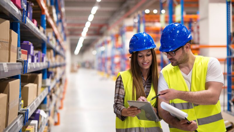 Warehouse workers checking inventory and consulting each other about organization and distribution of goods.