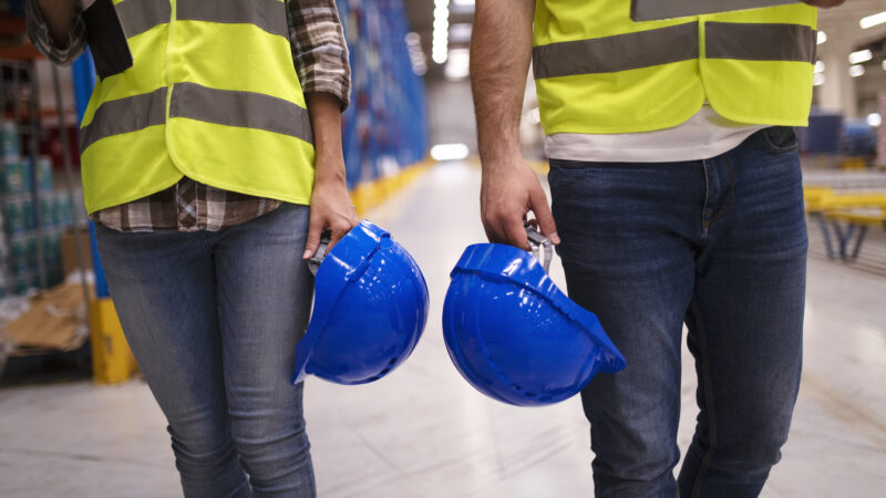 Two unrecognizable workers in reflective suit walking through warehouse and holding blue protective hardhats.
